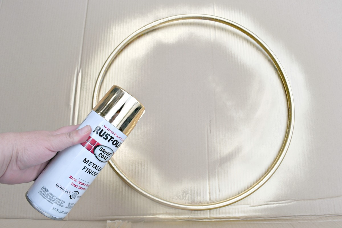 hand holding a can of gold spray paint over painted hula hoop on cardboard
