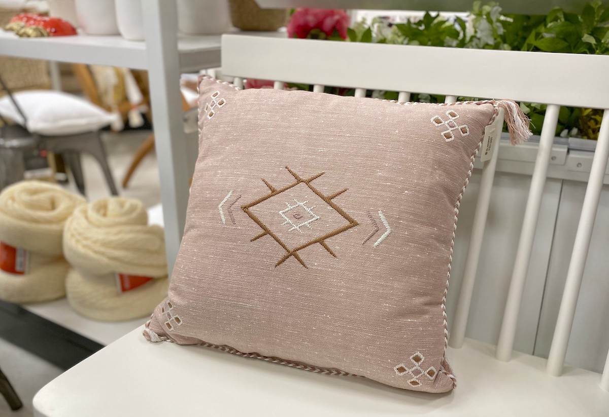 pink tribal pillow on white bench with home decor items in the background at store