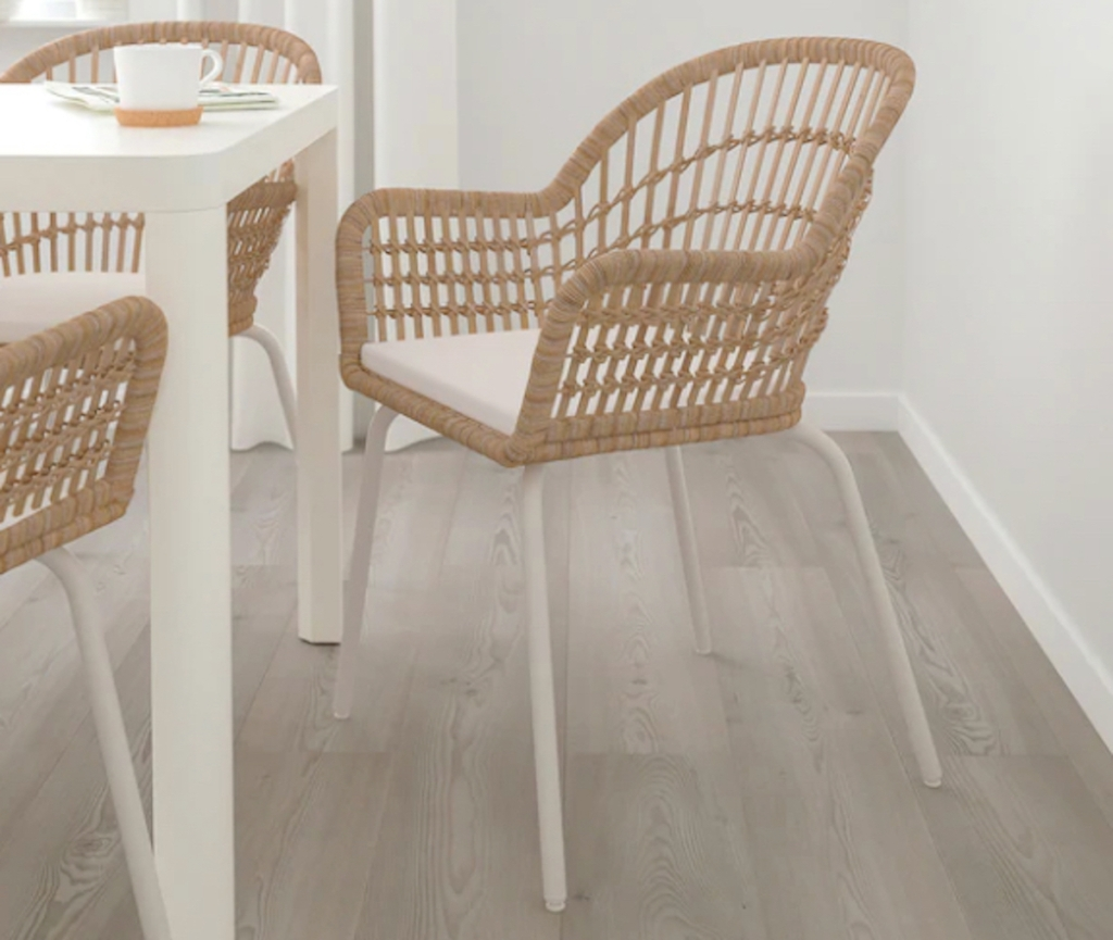 rattan chair with white cushion and legs sitting at dining room table