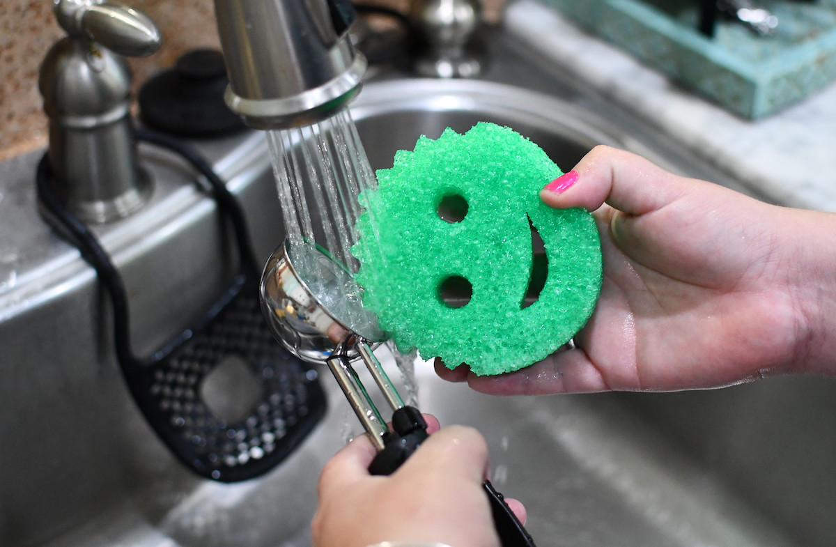 hand holding a green smiley face sponge and ice cream scoop