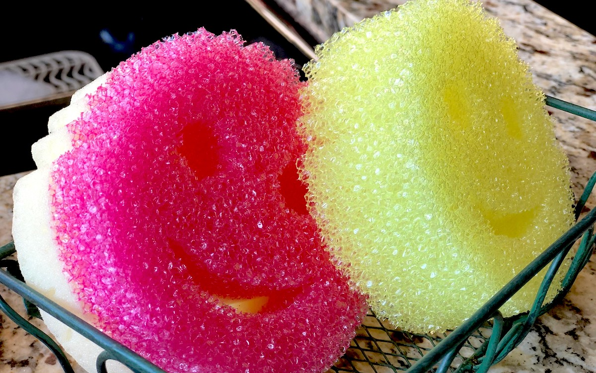 Pink and yellow smiley face scrub daddy sponges sitting in tray