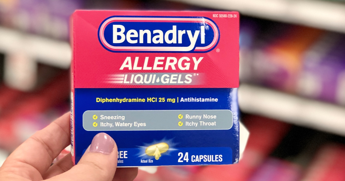 hand holding up a box of benedryl capsules in front of a store shelf