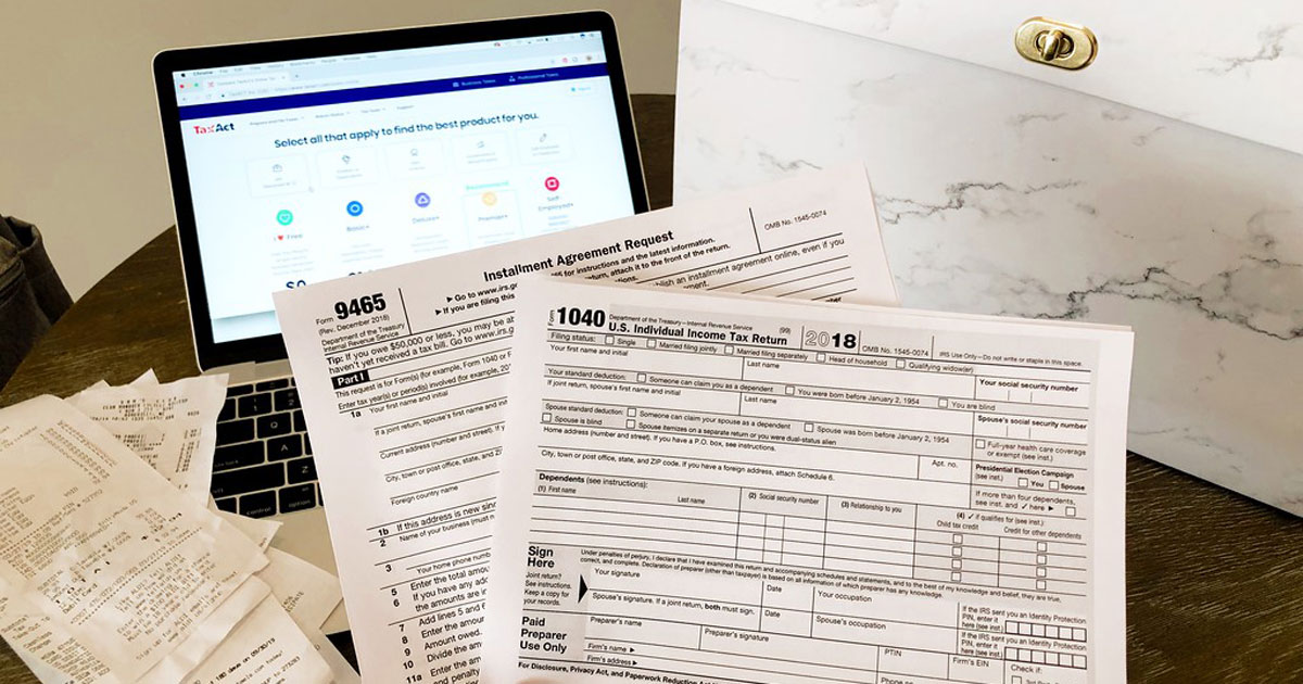 tax forms, receipts, and an open laptop