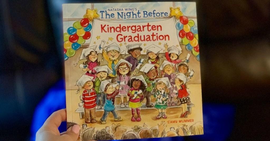hand holding the the night before kindergarten graduation book