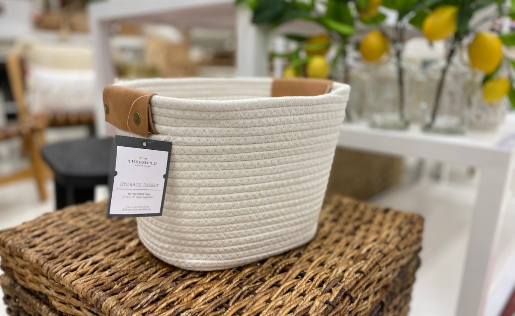 white basket with brown leather handles with white tag sitting in store on wicker furniture