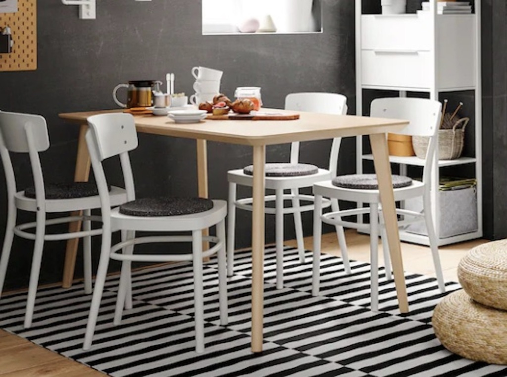 wood table in dining room with white chairs and black and white stripe rug