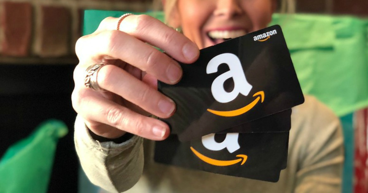 woman holding up amazon gift cards for Amazon cash