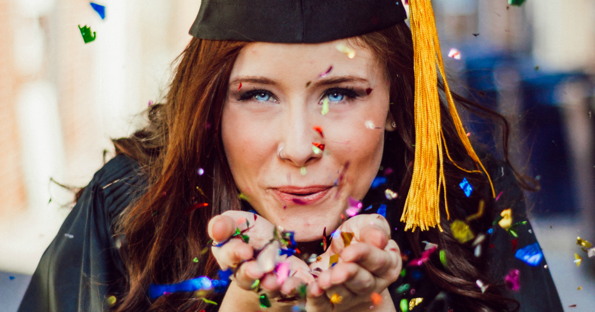 graduate blowing confetti from her open hands