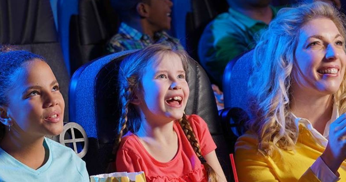 Kids smiling while watching a movie in the theater