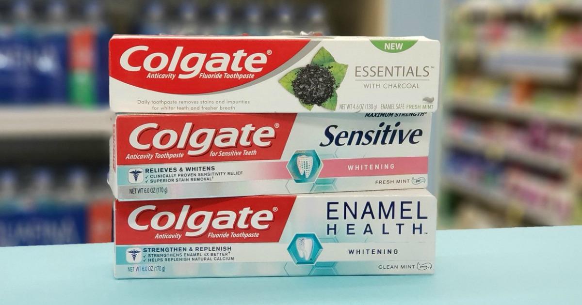 three tubes of colgate toothpaste on shelf