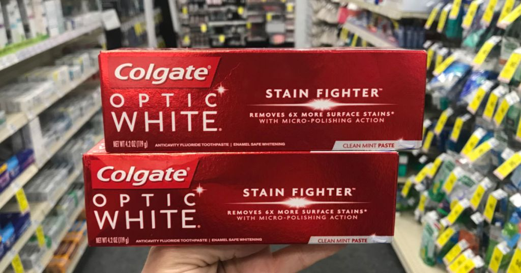 hand holding two boxes of Colgate optic white toothpaste