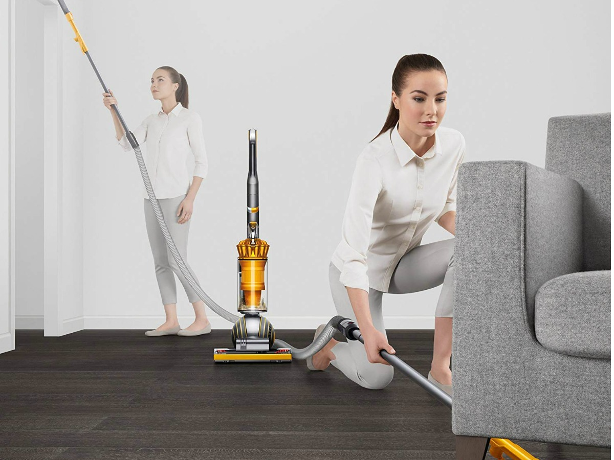 woman using vacuum wand to clean upper and lower parts of living area