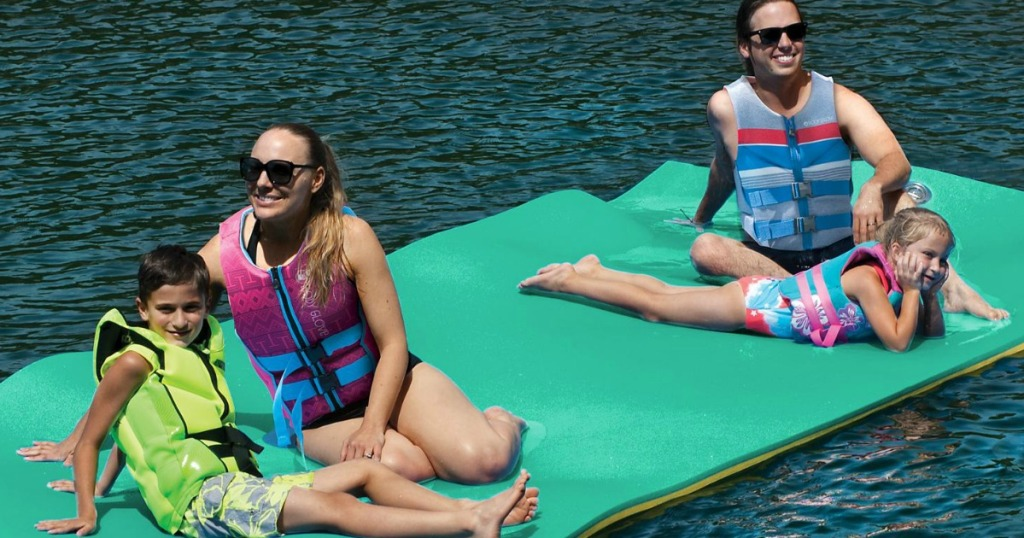 adults and kids sitting on green float in water