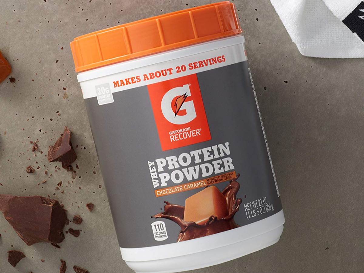Gatorade Whey Protein Powder Chocolate Caramel Container on cement with Chocolate chunks