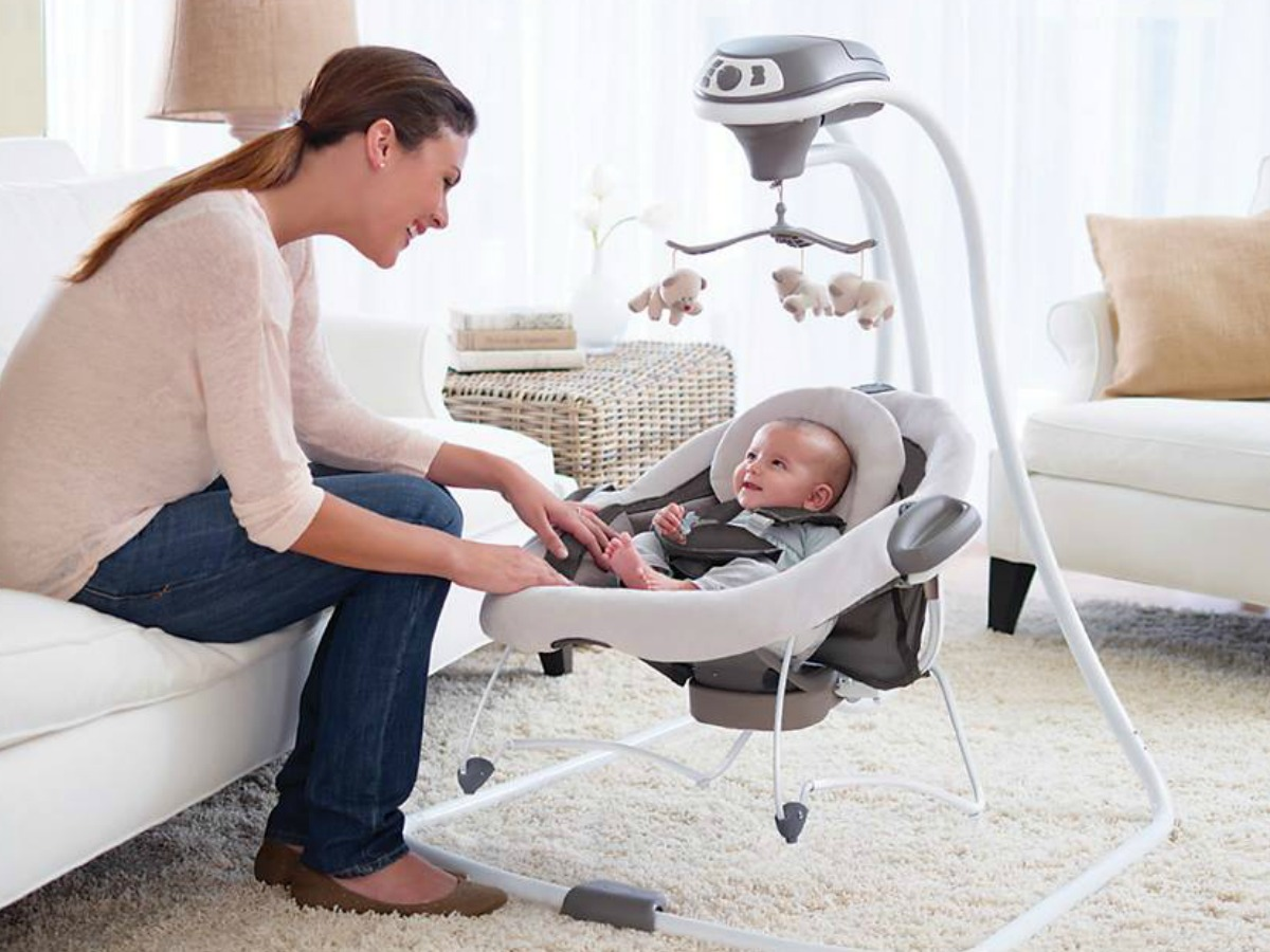 Mother playing with baby in Graco DuetSoothe Swing + Rocker