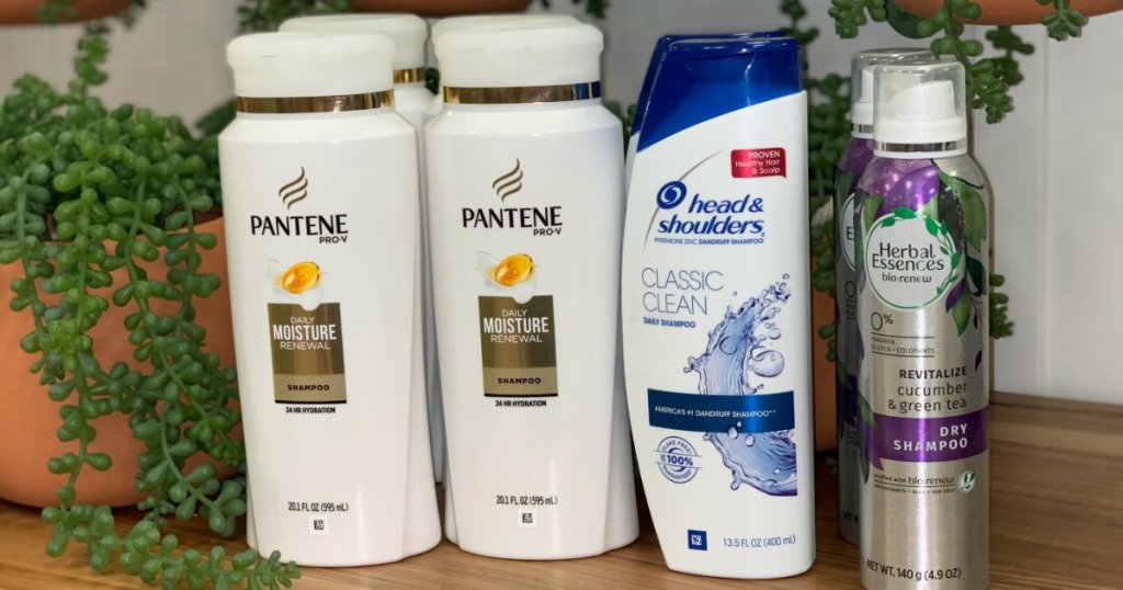 Pantene, Head & Shoulders and Herbal Essences hair care products on a shelf with plants