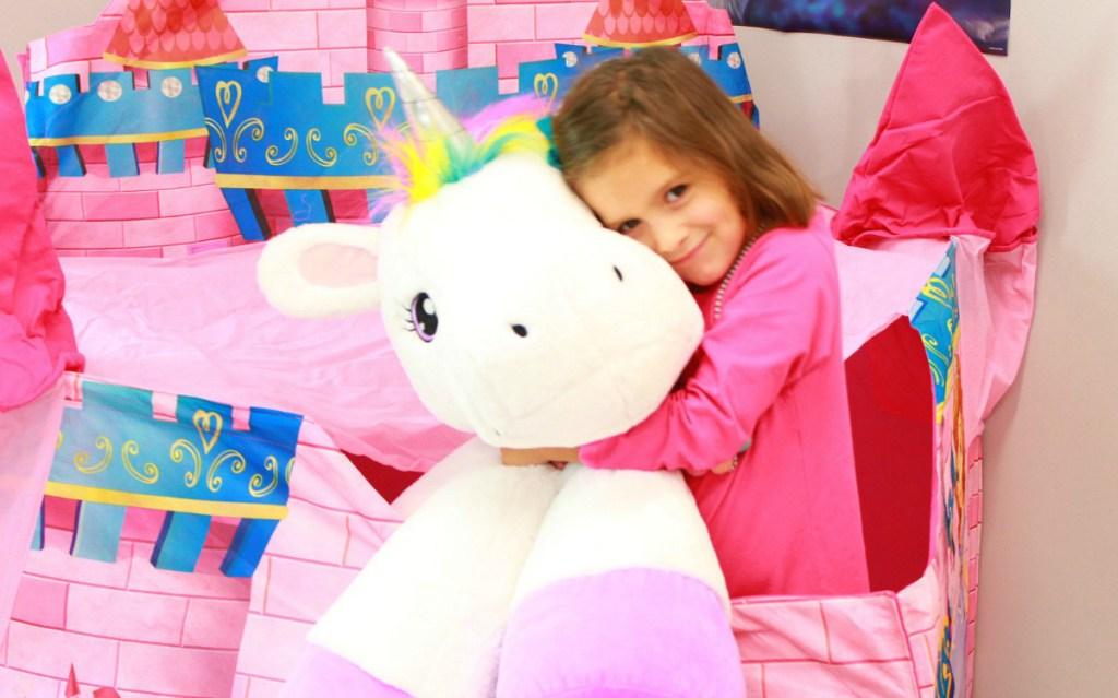 girl hugging stuffed unicorn plush