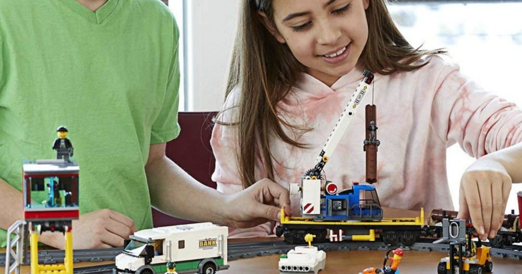 boy and girl playing with lego train set