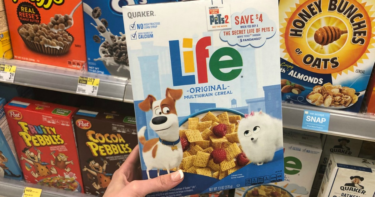 hand holding box of life cereal near store display