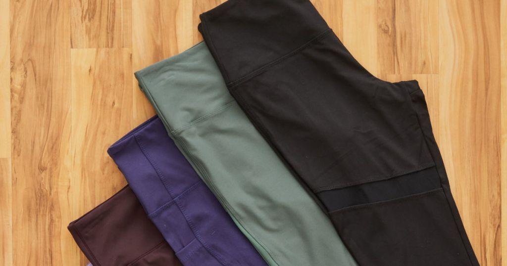 black, olive, blue, and plum marika leggings on wood floor