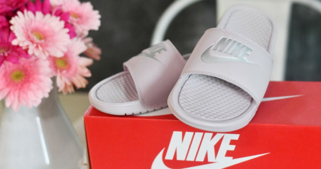 nike slides sitting on red shoebox with flowers