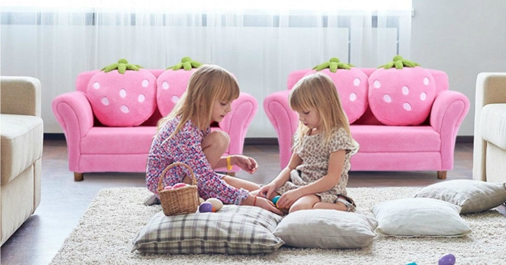 two girls sitting in front of pink couches with strawberry pillows