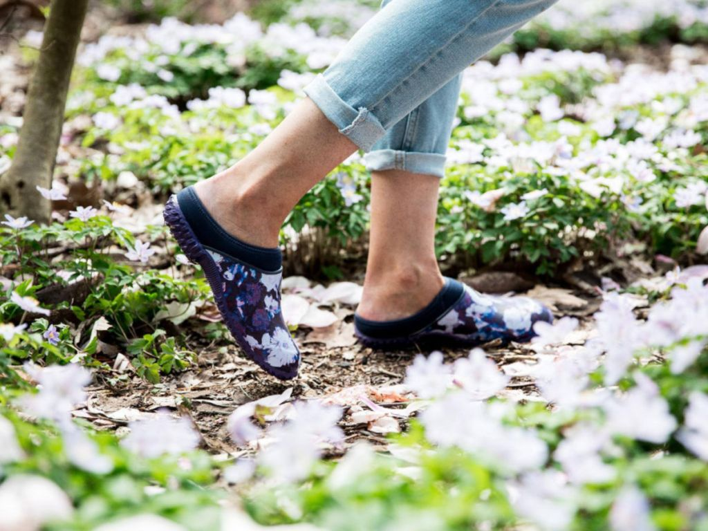 woman walking through grass with clogs on