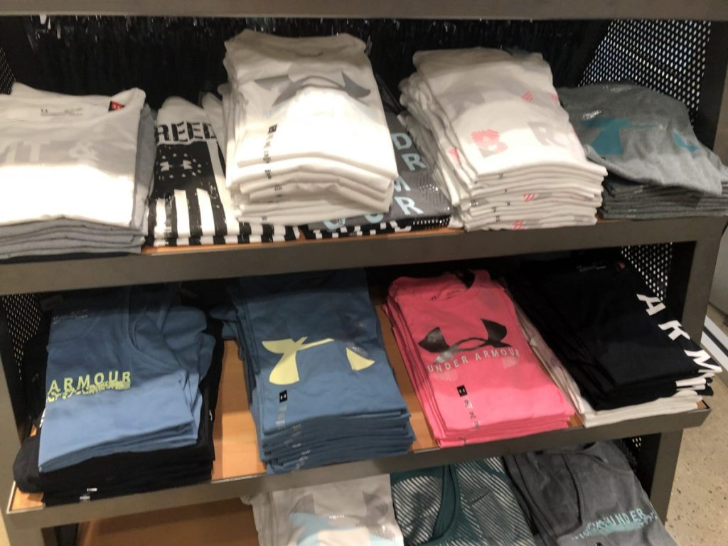 Under Armour Tees in various colors folded on a store display shelf