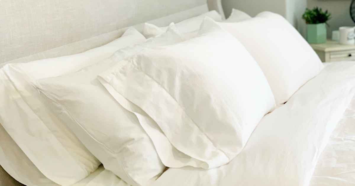 white bedding with three rows of white fluffy pillows