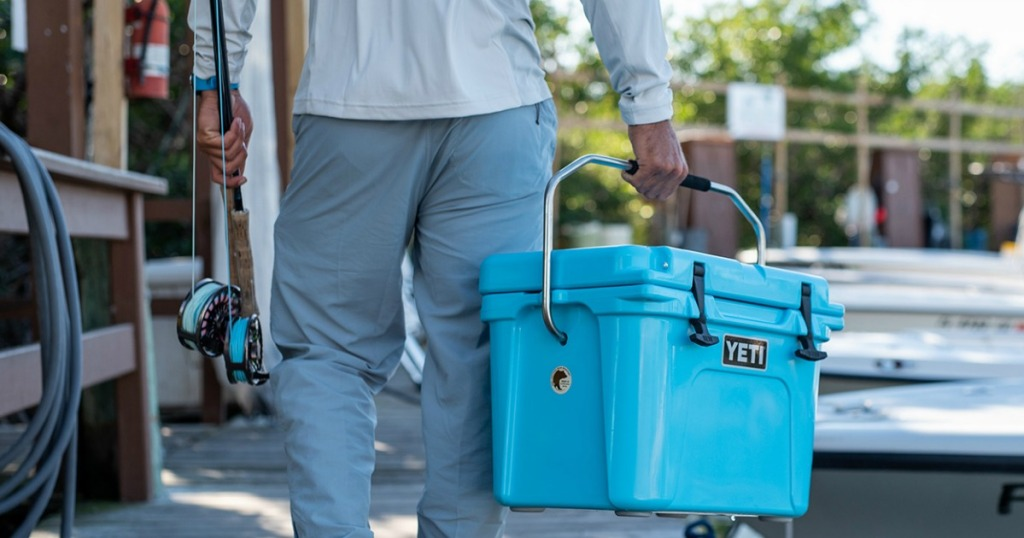Yeti Roadie Cooler Being carried by man with fishing pole on pier
