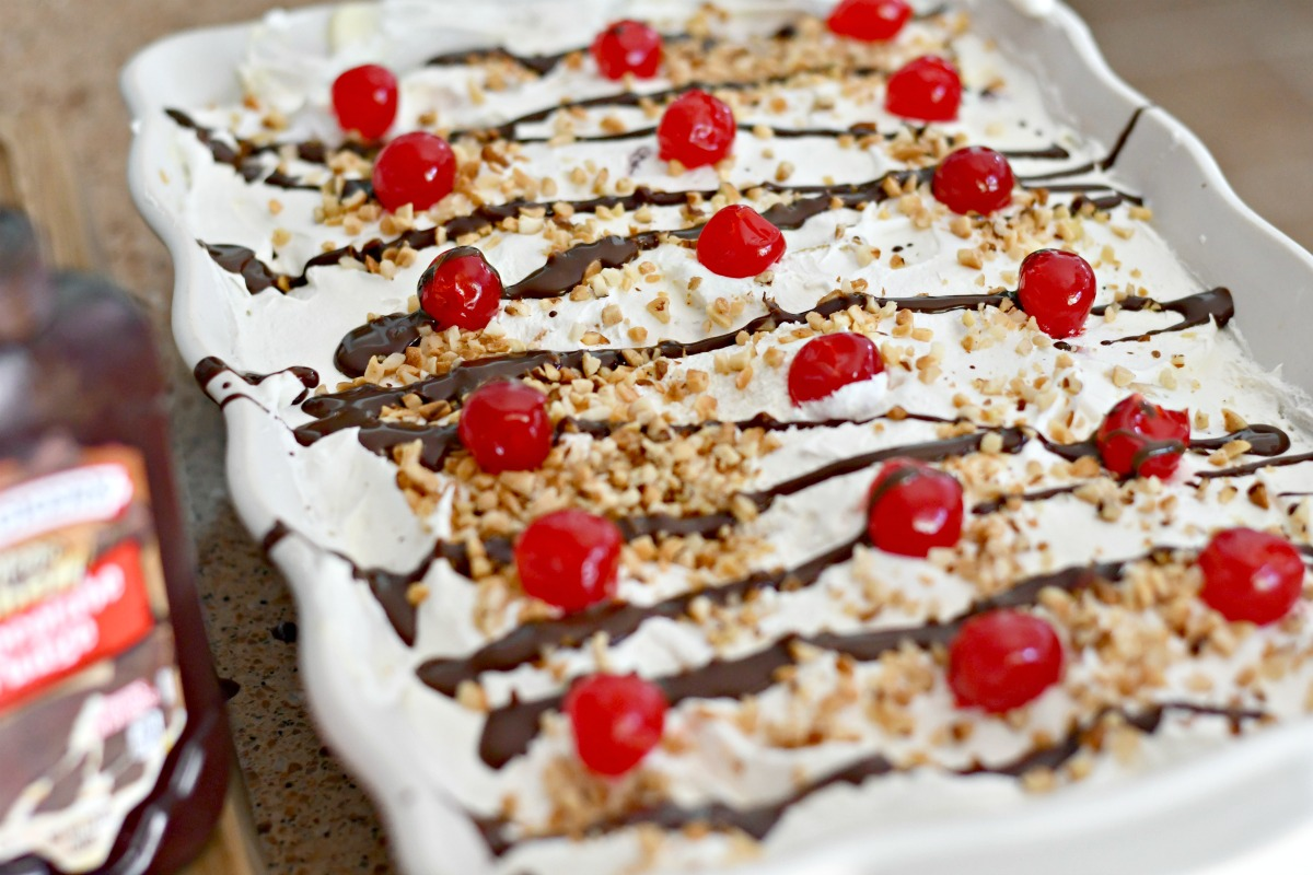adding chocolate and cherries to banana split pudding dessert