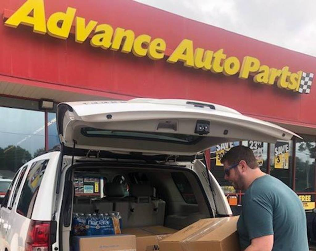 man putting boxes inside white car trunk with advance auto parts store sign in background