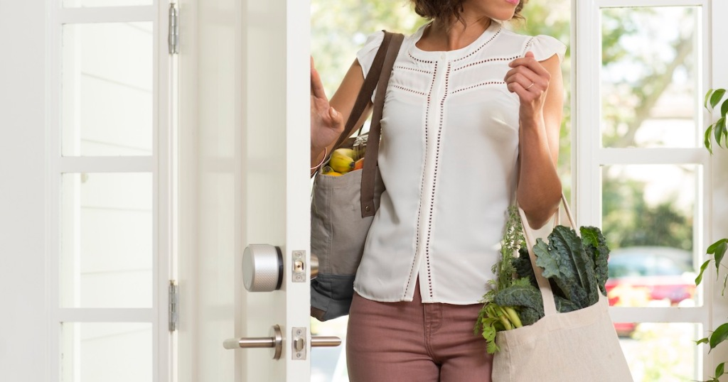 woman walking through front door with grocery bags on arms