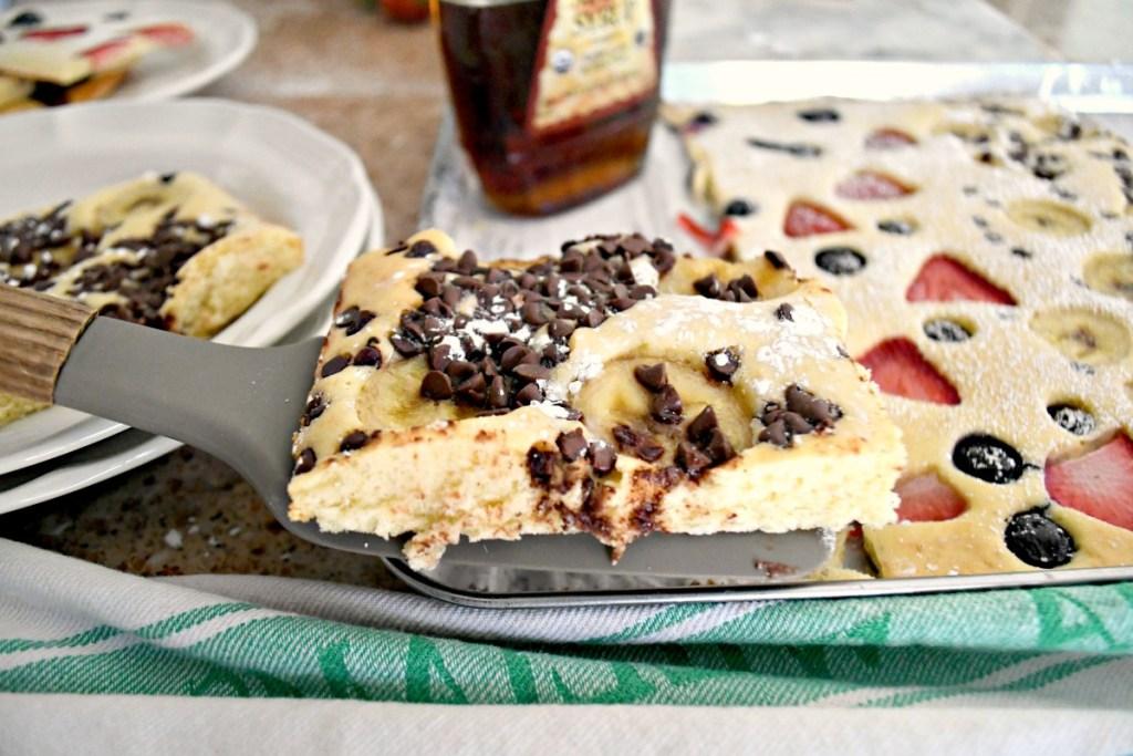 serving a slice of banana chocolate chip sheet pan pancakes