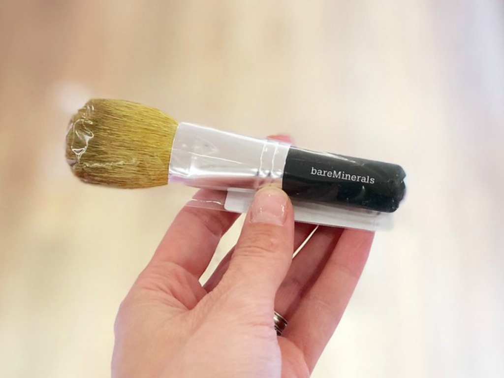 Hand holding bareMinerals makeup brush with blurred background