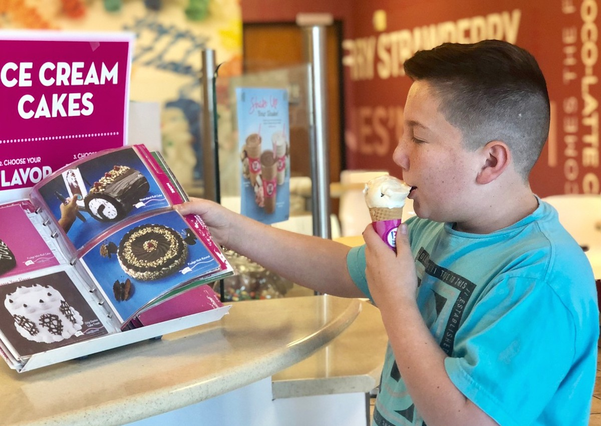boy eating a scoop of vanilla cone ice cream looking at book with cakes