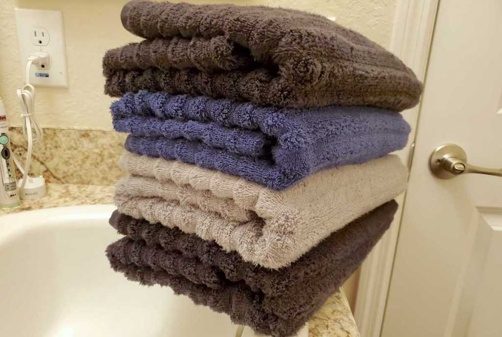 stack of brown and blue bath towels on bathroom sink