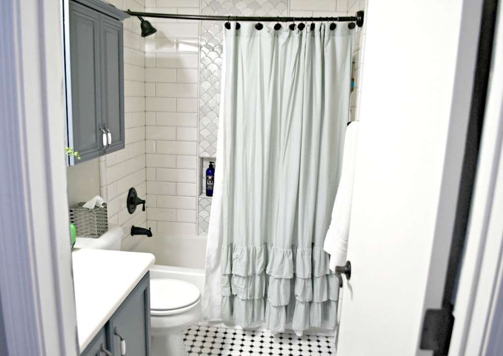 bathroom with ruffle shower curtain and white tile