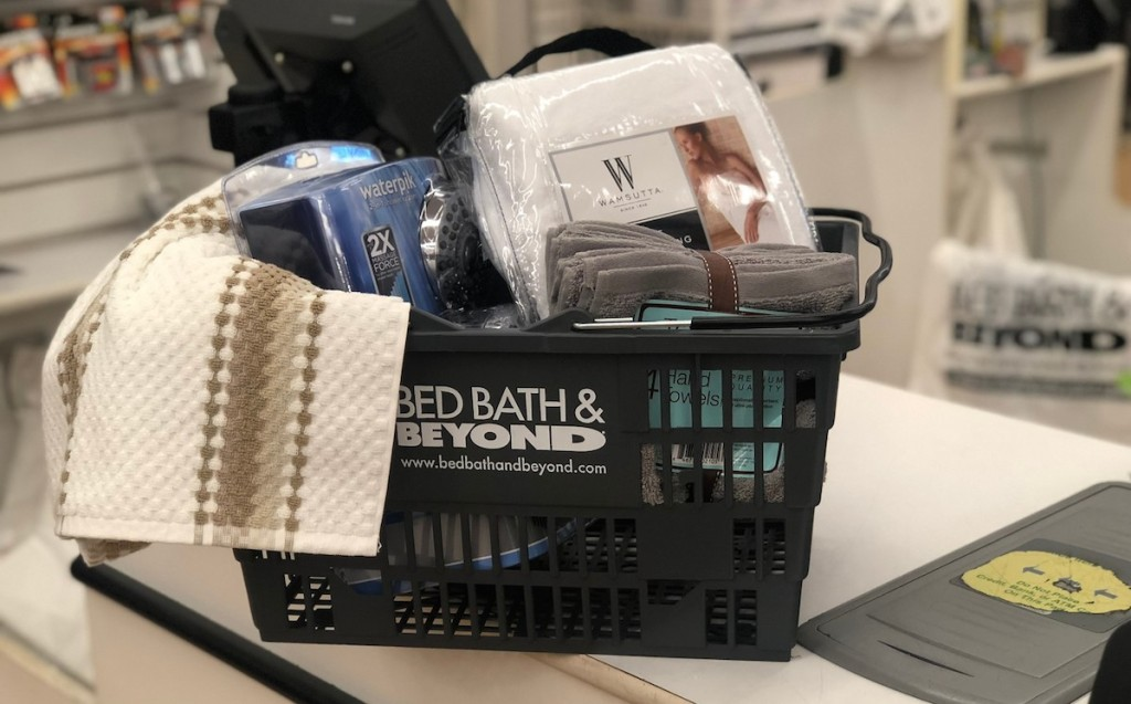 bed bath and beyond basket with towels and sheets inside on store checkout counter