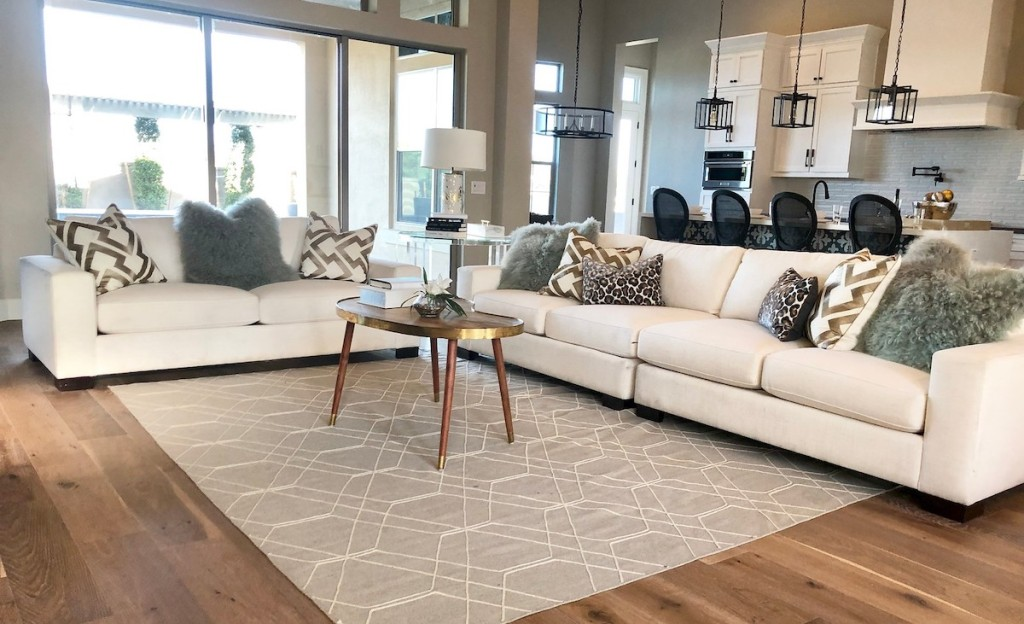 living room with white couches and various sizes and colored pillows