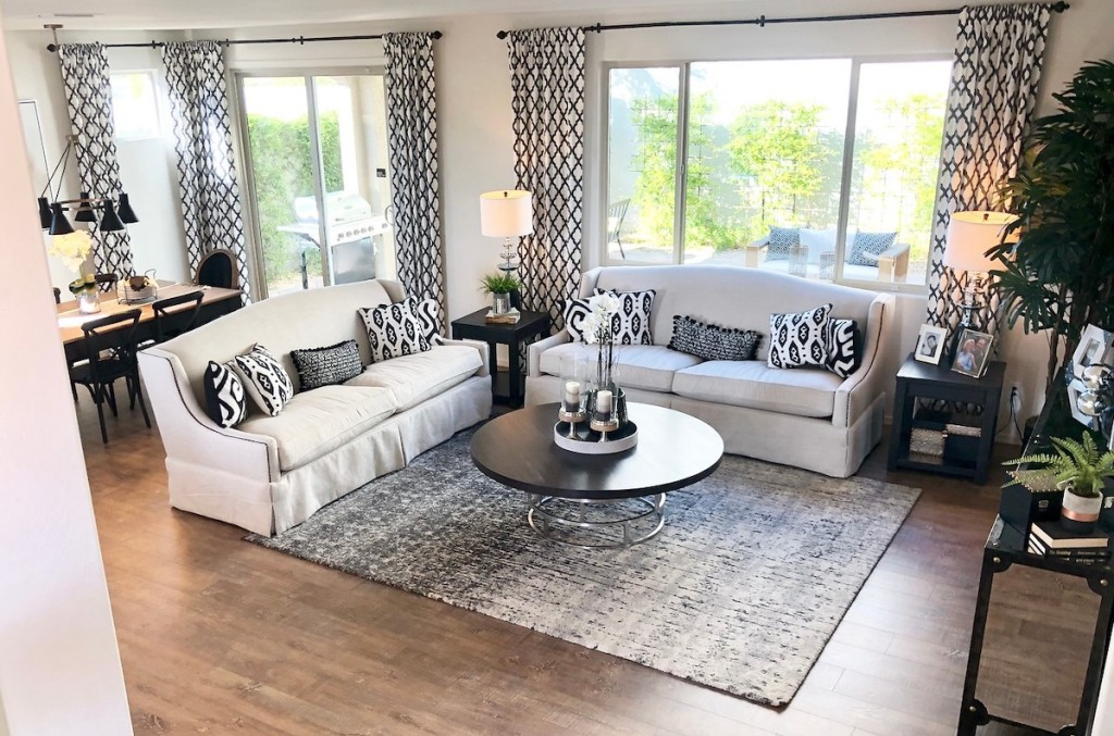 living room and dining room with furniture and tall curtains