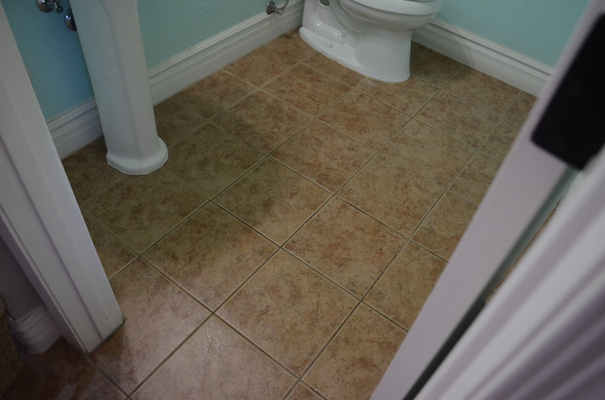 bathroom tile floor with dirty grout