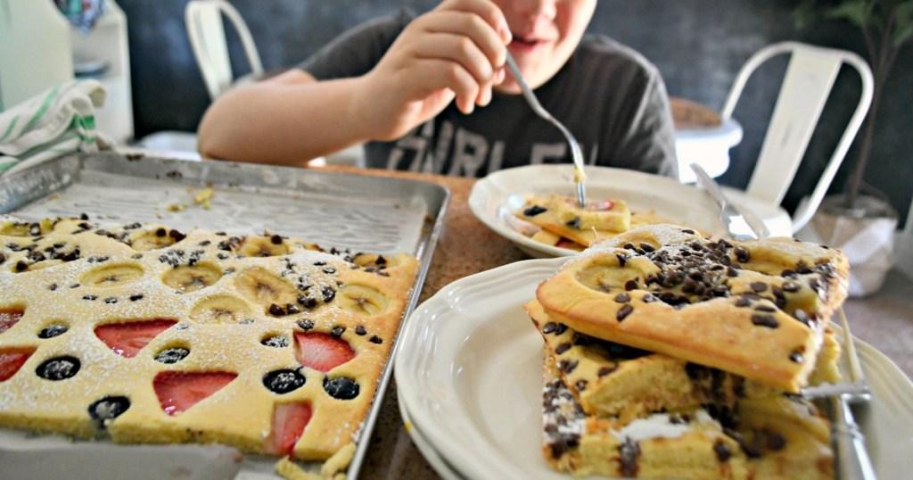 boy taking a bite of sheet pan pancakes