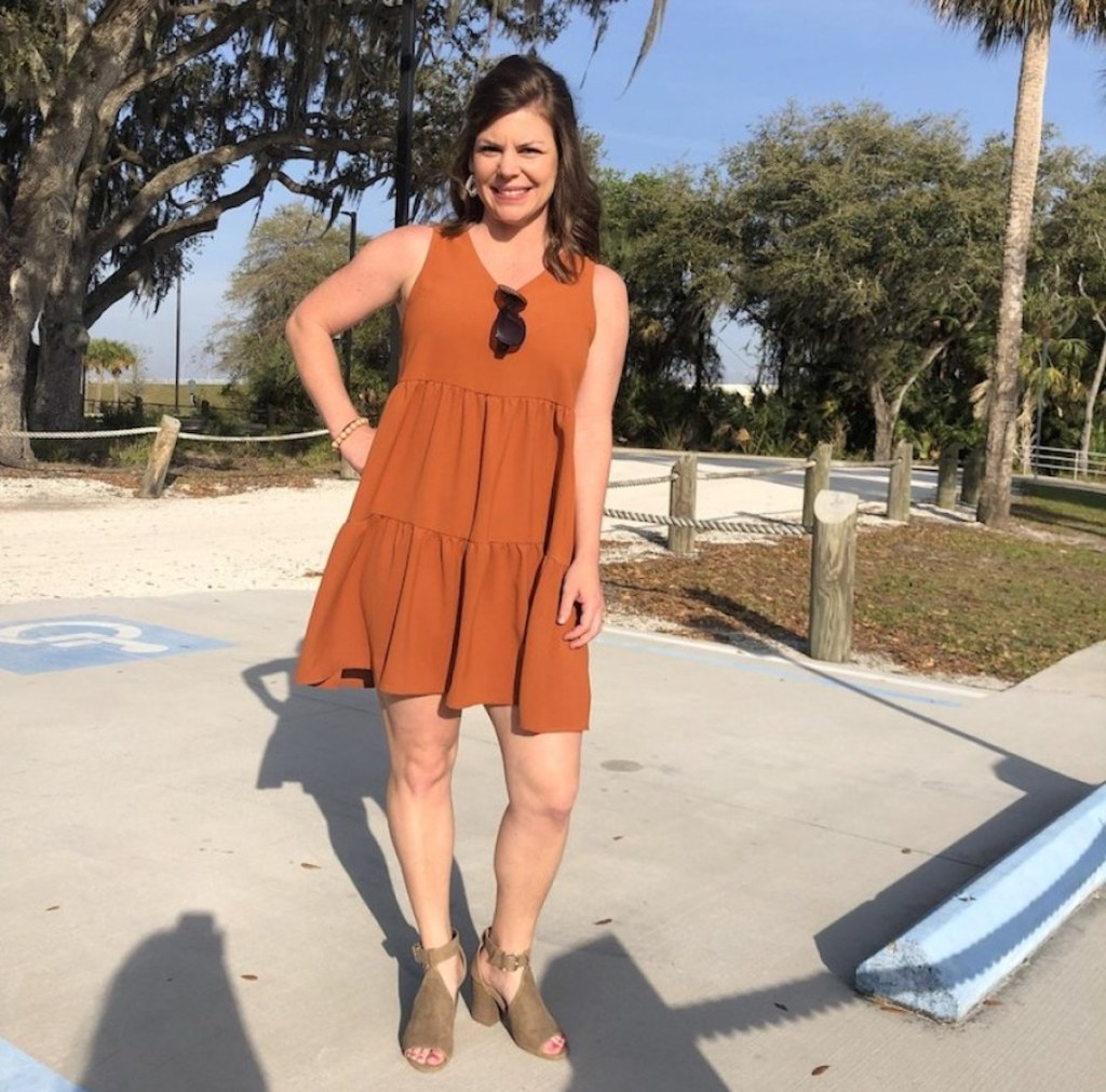 woman standing outside in parking lot smiling wearing orange dress