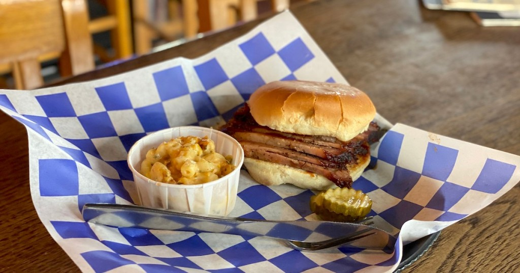 brisket sandwich and side of mac and cheese sitting in blue and white checked basket