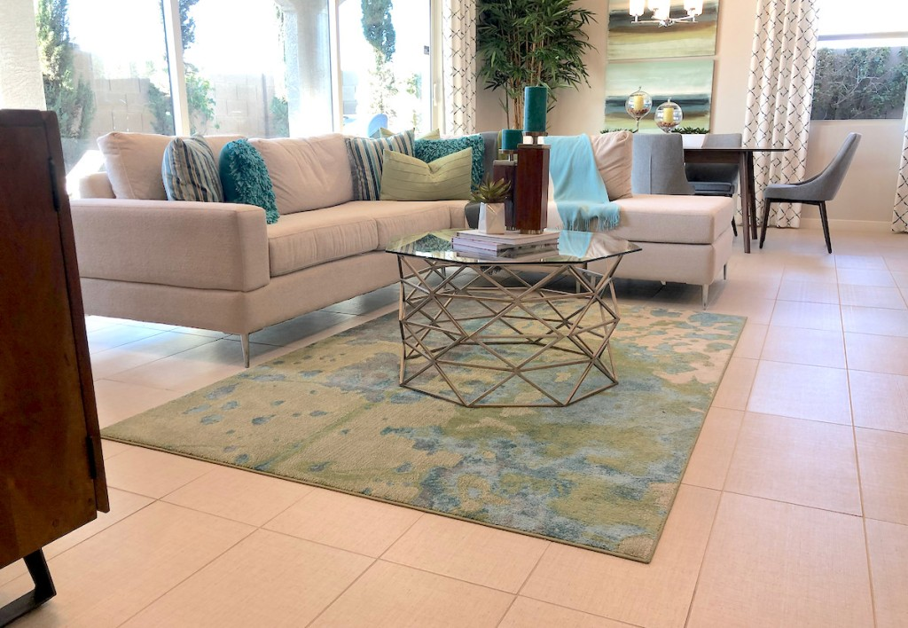 living room with blue and green rug beige sofa and glass coffee table