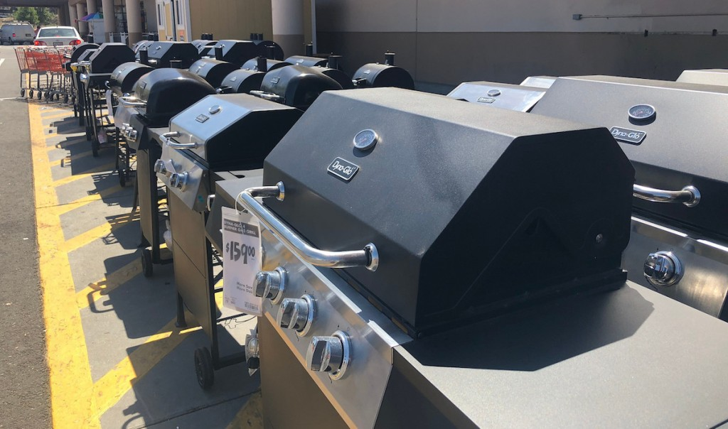 various types of outdoor grills lined up outside on pavement in front of home depot store