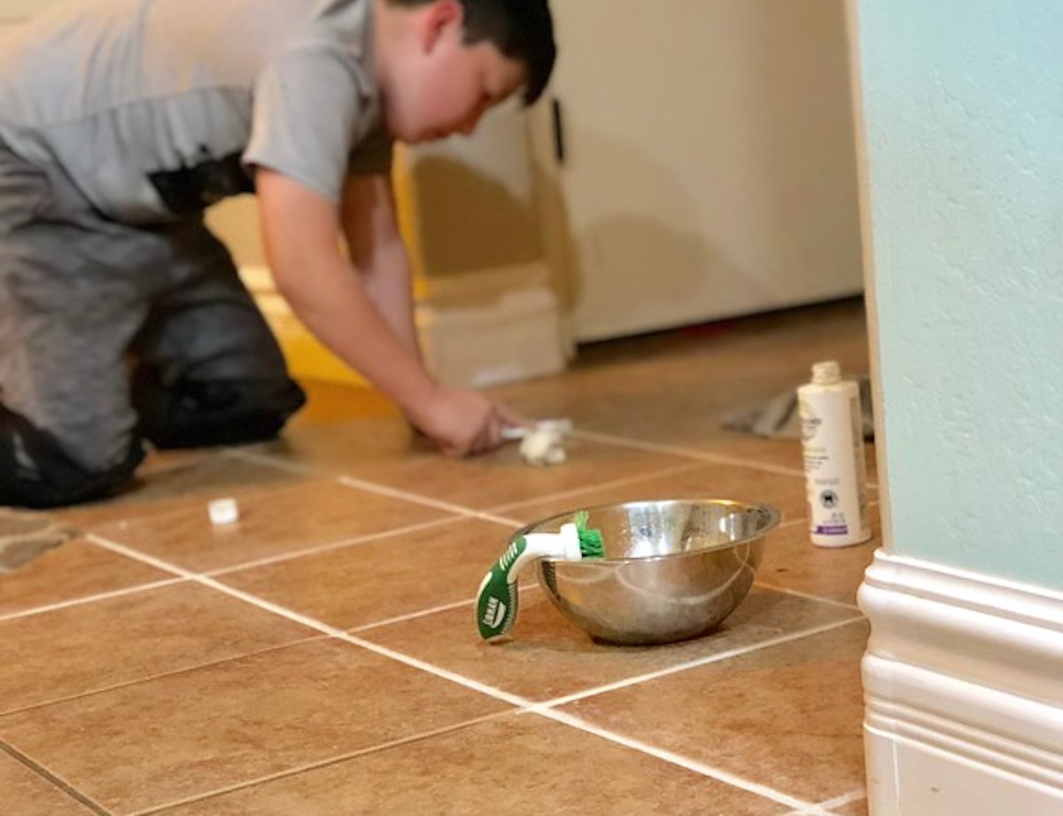 boy with toothbrush applying white grout sealant on tile floor