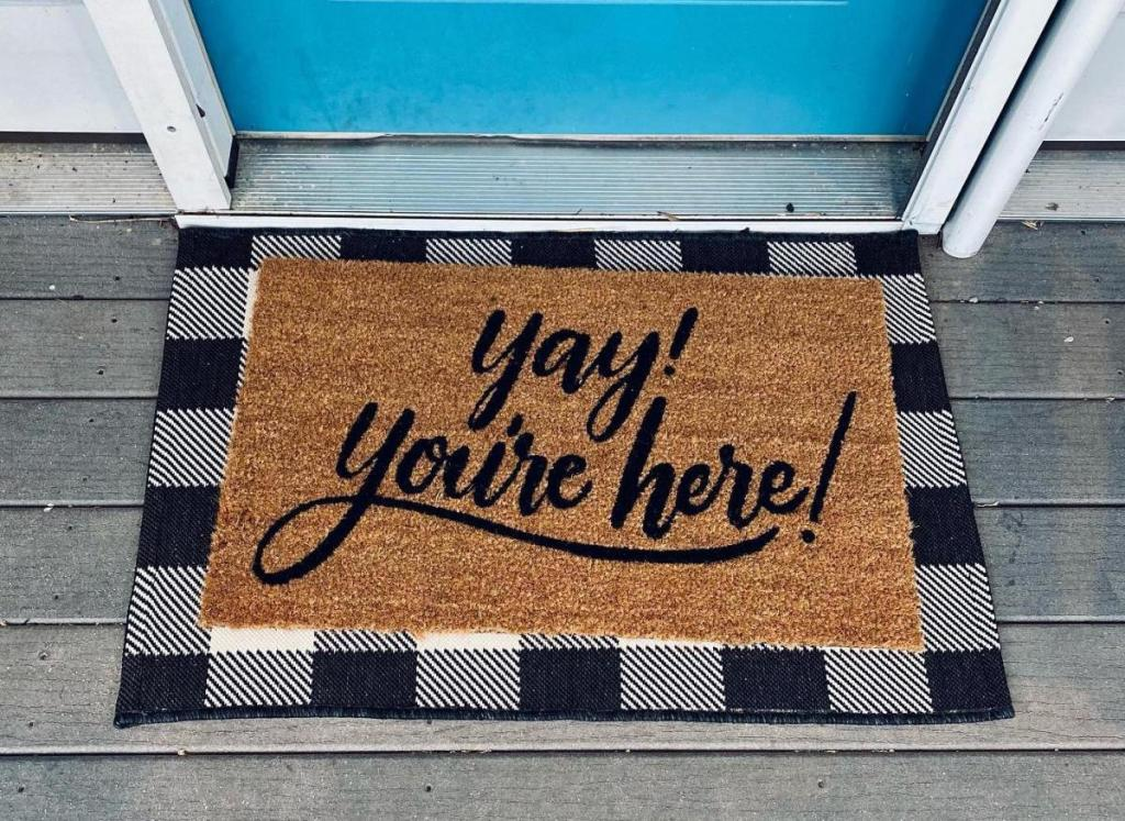 yay you're here and white and black check doormat at blue front door
