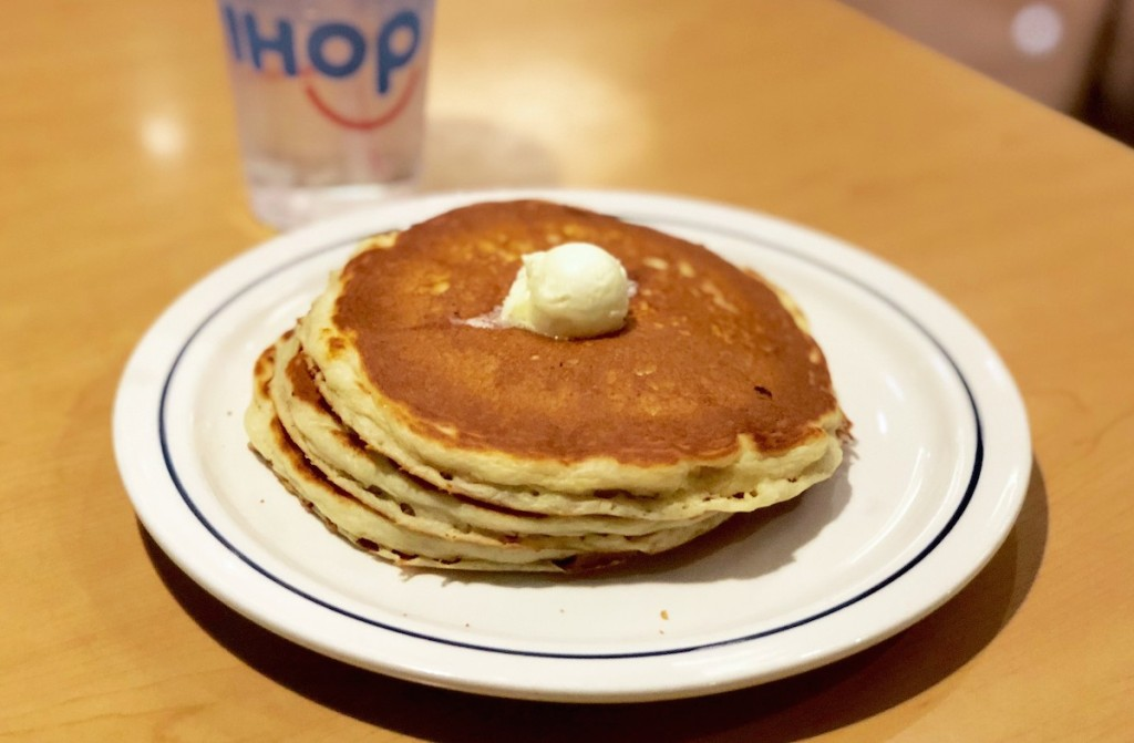 white plate with stack of plain buttermilk pancakes and scoop of butter on table